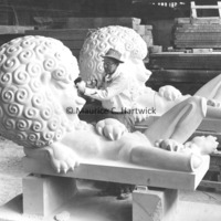 A carver works on the limestone lion for The Lion and Mouse with the plaster model in the background.jpg
