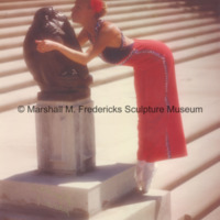 An unidentified woman pretends to kiss The Thinker at Cranbrook Art Museum.jpg
