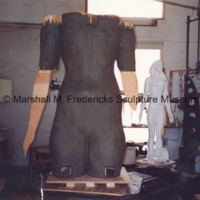 Front view of the plasteline covered armature of the female figure for Star Dream Fountain with the plaster model in the background.tif