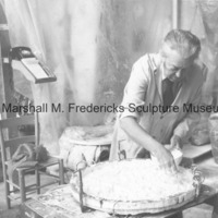 Marshall Fredericks adds plaster to the mold for an unidentified medal in his Royal Oak studio.tif