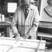 Marshall Fredericks adhere metal supports to an unidentifed relief in his Royal Oak studio.tif