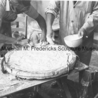 Marshall Fredericks and an assistant add plaster to the mold for an unidentified medal in his Royal Oak studio.tif