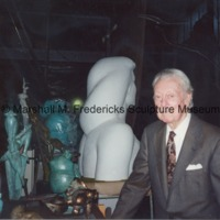Marshall Fredericks poses with the plaster head and shoulders from the female figure for Star Dream Fountain and several small bronze sculptures in the studio.tif