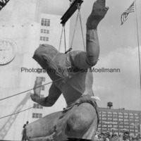 The Spirit of Detroit is lowered onto the ground in front of a crowd of spectators.jpg