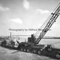 The Spirit of Detroit on a truck beside the Detroit River with the Ambassador Bridge in the background.jpg