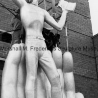 Workers prop up Youth in the Hands of God against scaffolding prior to its installation on the facade of the Marshall M. Fredericks Sculpture Museum.tif